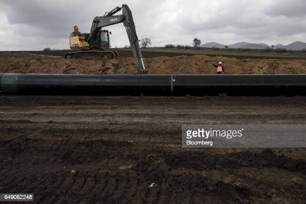A worker from SpiecapagAktor JV supervises as a Volvo AB crawler excavator lowers welded pipe sections into a trench at the 685km point during the...