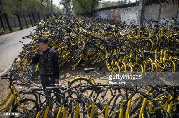 A worker from the bike share company Ofo stands amongst piles of damaged bikes at a makeshift repair depot for the company where thousands of...