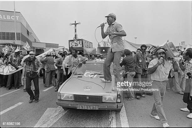 A worker from the Confederation Generale de Travail trade union speaks to the crowd from the hood of a car during a strike outside the Talbot car...