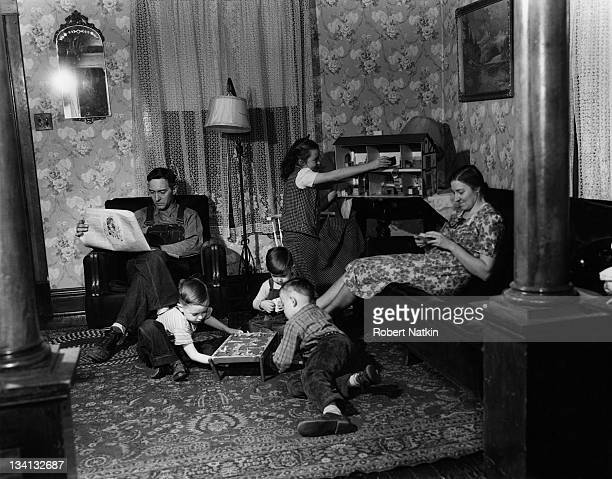 A worker from the discount chain store Goldblatt's relaxes with a newspaper while at home with his wife and four children Chicago 1951