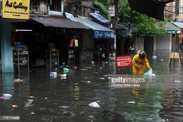 A worker from the municipal environmental service collects garbage on a flooded street in the old tourist quarter following heavy rains on August 8...
