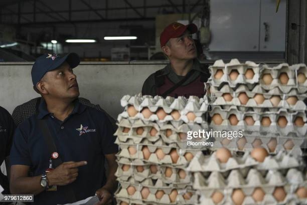 A worker from the National Superintendence for the Defense of the Socioeconomic Rights and a member of the Bolivarian National Guard verify the sales...