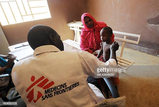 A worker from the NGO Doctors Without Borders speaks with a sick child in Gao in the north of Mali on February 4 2013 Schools reopened today in Gao...