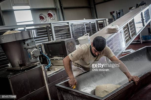 A worker from the Turkish Humanitarian Relief Foundation prepares dough for bread made in the specially setup Syrian bakery for distribution to...