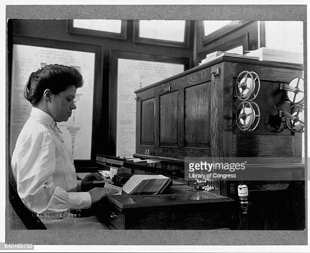 A worker from the United States Census Bureau feeds keypunch cards into a card reader The holes on the cards represent census information which can...