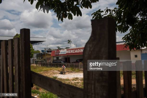 Worker gathers dirt in a wheelbarrow near the Venezuelan border in Pacaraima, Brazil, on Wednesday, April 10, 2019. Venezuelan refugees looking for...