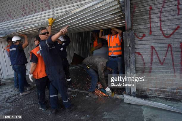 Worker gestures as repairing a looted supermarket on November 28 2019 in Santiago Chile Violent protests looting and arson occurred yesterday in...