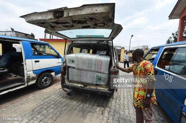 Worker gestures towards a van loaded with ballot boxes for distribution to wards at the Independent National Electoral Commission central office in...