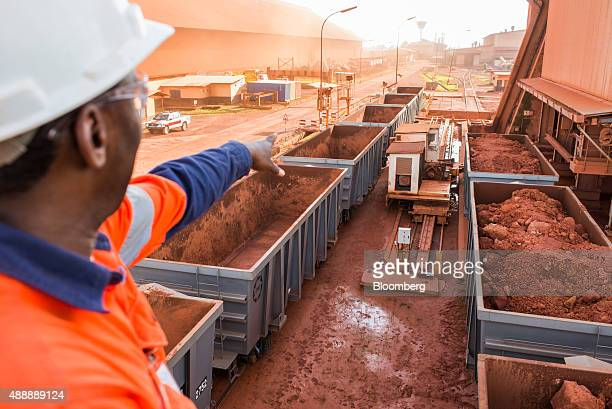 A worker gestures towards railway freight wagons loaded with bauxite which is refined into aluminum at a treatment plant operated by Compagnie des...
