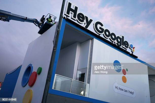 Worker get ready to clear up water collected on a tarp atop of the roof of the Google booth which was closed on the first day of CES 2018 at the Las...