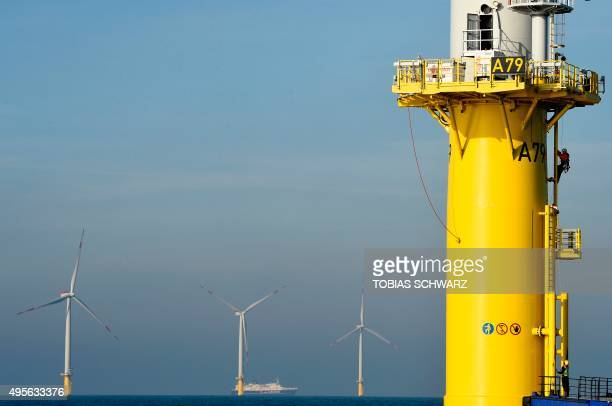 A worker gets off a wind turbine of the German offshore wind farm 'Amrum Bank West' owned by German energy company EON near the Heligoland...