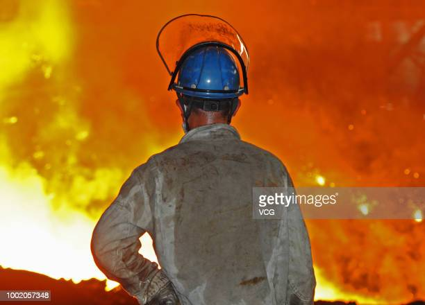 A worker pries up molten cast iron from a blast furnace at a plant of Dongbei Special Steel Group on July 17 2018 in Dalian Liaoning Province of...