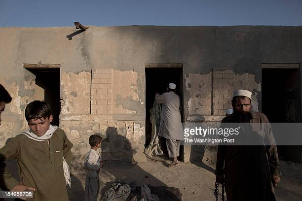A worker gives a blanket to 'a patient' at the Mia Ali Sahib shrine outside Jalalabad Afghanistan on October 19 2012 Relatives bring those with a...