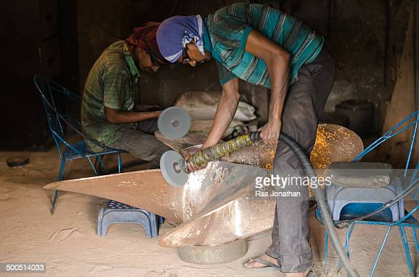 Worker gives a finishing touch to a ship propeller built at a metal workshop beside the river Buriganga. Shipbuilding is a growing industry in...