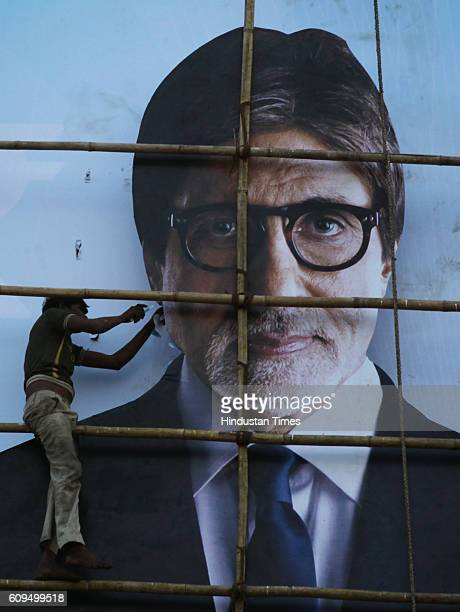 A worker gives fixes a billboard at the Mahim Causeway advertising the TV show Kaun Banega Crorepati hosted by actor Amitabh Bachchan The show will...
