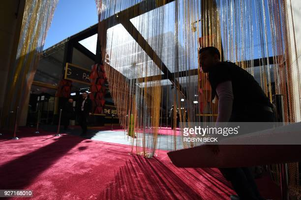 A worker gives the finishing touch to the red carpet a few hours before the 'Oscars' the 90th Annual Academy Awards on March 4 in Hollywood...