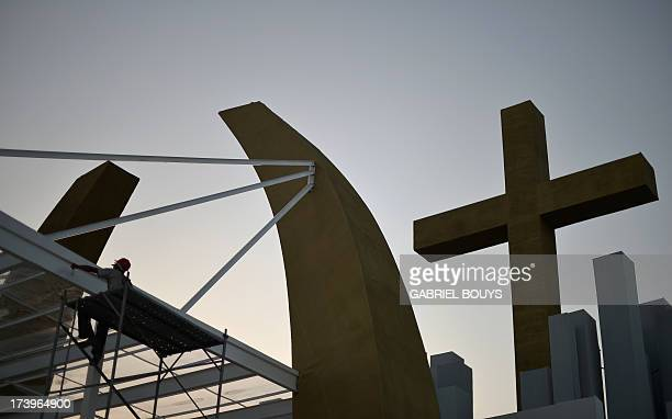"""Worker gives the finishing touches to the stage constructed for a papal mass and youth vigil to be held on """"Campus Fidei"""", a 300-hectare vacant lot..."""