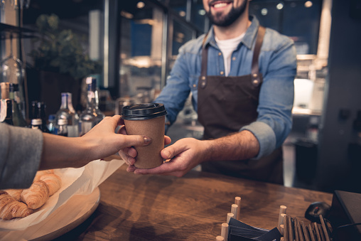Worker giving mug of beverage to woman 874876398