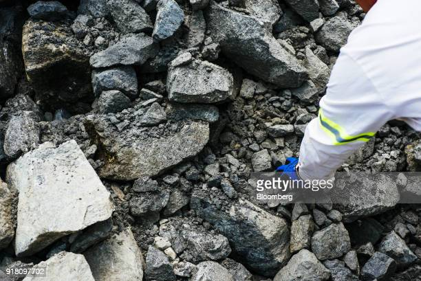 A worker grabs a rock from a stockpile of raw aluminum containing ore mined from the Upper Group 2 Reef platinum rich layer at the Northam Platinum...