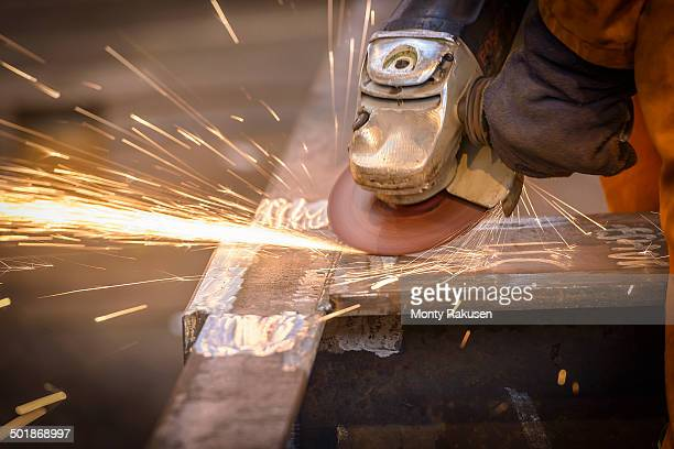 Worker grinding metal construction in marine fabrication factory