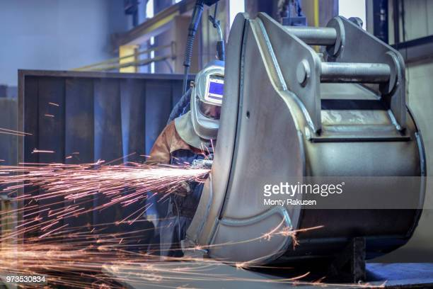 worker grinding metal in engineering factory - monty rakusen stock-fotos und bilder
