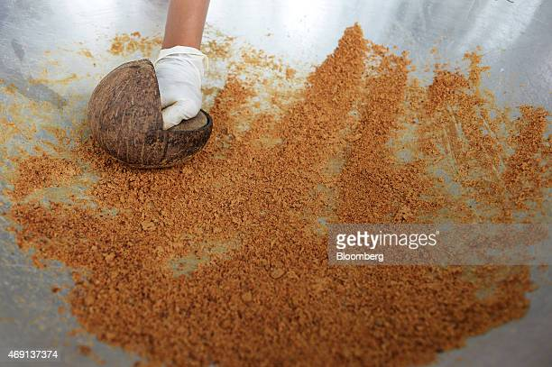 A worker grinds coconut palm sugar at the PT Bio Takara factory in Purwokerto Central Java Indonesia on Wednesday March 11 2015 Central Java's...