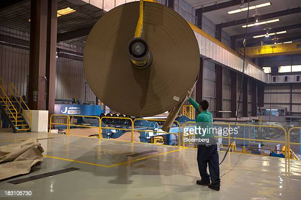 A worker guides a roll of kraft paper toward the cutting machine at the BioPappel Kraft manufacturing and recycling plant in Tizayuca Hidalgo Mexico...