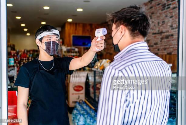 コビッド-19パンデミック中にスーパーマーケットで買い物をする前に保護マスクを着用した顧客の温度スキャナチェック熱を保持する労働者の手 - フェイスシールド ストックフォトと画像