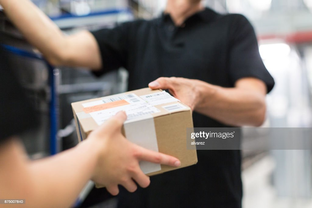 Worker handing over a package to colleague : Stock Photo