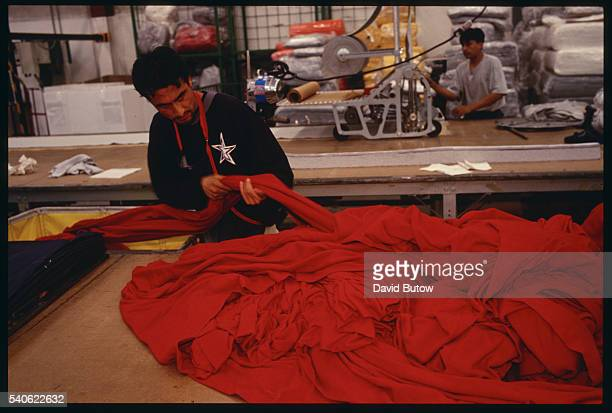 A worker handles a long strip of cloth at the Qualytel de Puebla clothing manufacturing plant in Puebla Mexico Qualytel produces garments for such US...