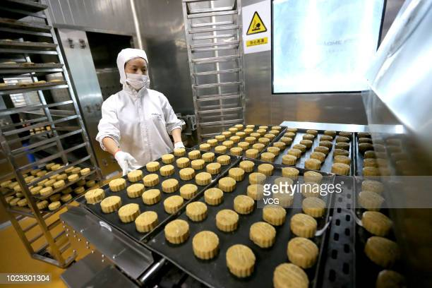 A worker handles a tray of mooncakes at a mooncake factory on August 21 2018 in Meishan Sichuan Province of China Mooncake is the traditional food...