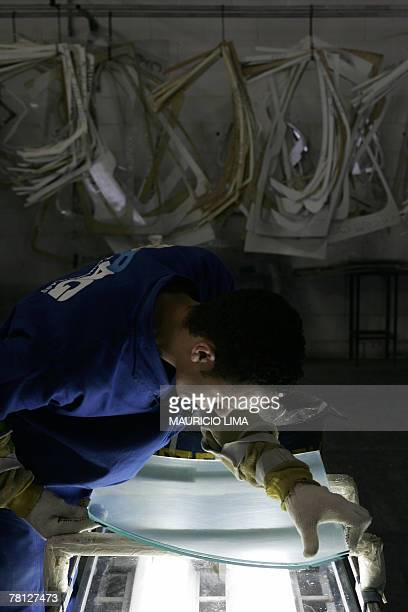 A worker handles an armored glass at a vehicle armoring factory in Itaquaquecetuba some 40 km north from Sao Paulo Brazil 08 November 2007 AFP...