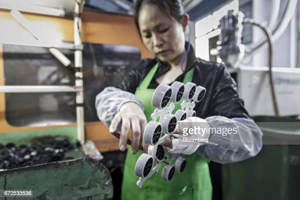 A worker handles casters wheels at a workstation that will be replaced by an industrial robot at a factory operated by the Guangdong Shiyi Furniture...