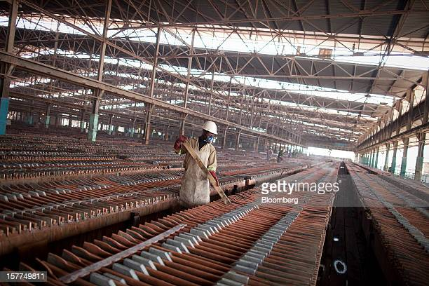 A worker handles copper sheets during electrolytic refining at the metallurgical plant in Katanga Mining Ltd's copper and cobalt mine in Kolwezi...