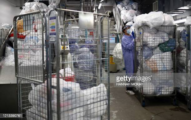 A worker handles dirty laundry in the laundry and linen room at the Royal Blackburn Teaching Hospital in Blackburn northwest England on May 14 as...