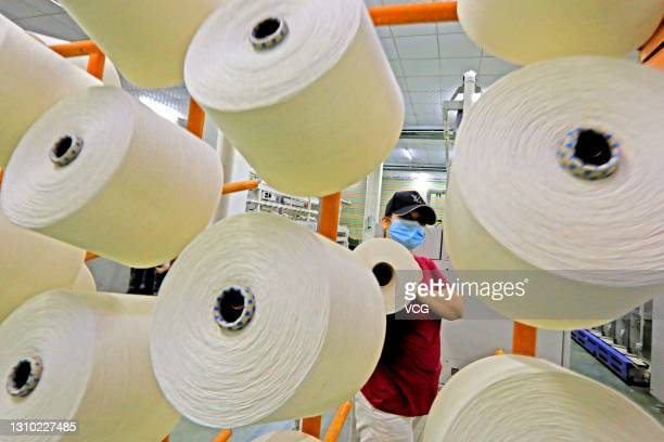 Worker handles spools of yarn on a production line at a workshop of Xinjiang Xieyi Textile Technology Co., Ltd on March 30, 2021 in Kuqa, Xinjiang...