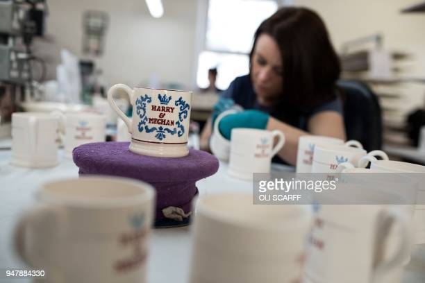 A worker handpaints a commemorative mug with a message celebrating the forthcoming wedding of Britain's Prince Harry and his US fiance Meghan Markle...