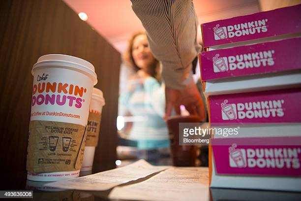 Worker hands cups of coffee and boxes of donuts to a customer during the opening of the new Dunkin' Donuts Inc. Restaurant in Mexico City, Mexico, on...