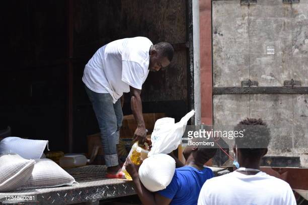 Worker hands out bags of rice and cooking oil to residents at a World Food Programme distribution site in Port-Salut, Haiti, on Tuesday, Aug. 24,...