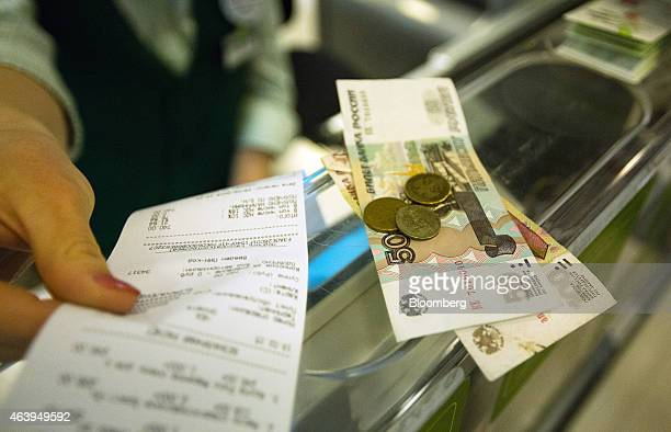 A worker hands over a receipt together with ruble banknotes and coins to a customer in payment for goods at the checkout desk of an Azbuka Vkusa OOO...