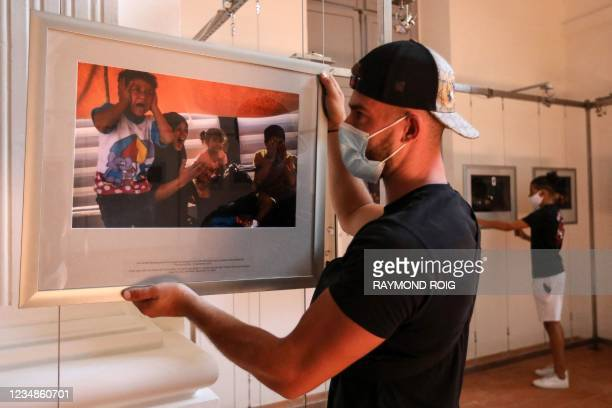 """Worker hangs photos for the exhibition """"The last days of Moria camp"""" of AFP photojournalist Angelos Tzortzinis ahead of the 33rd edition of the Visa..."""