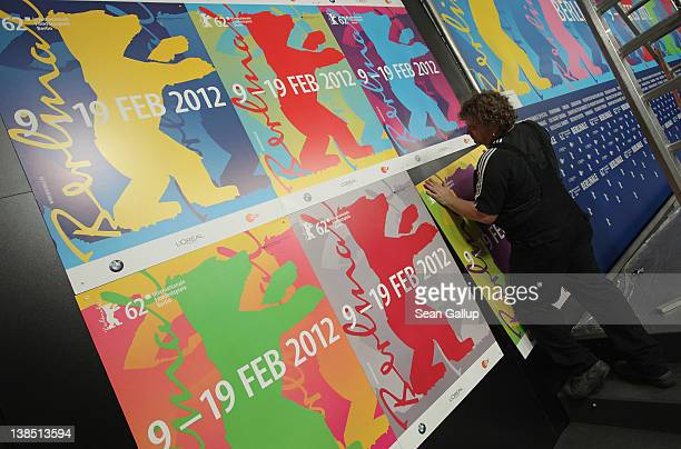 A worker hangs posters in the press conference room the day before the opening of the 62nd Berlinale International Film Festival on February 8 2012...