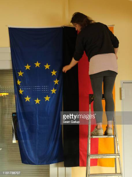 A worker hangs the European Union and German flags before the opening of a polling station in European parliamentary elections on May 26 2019 in...