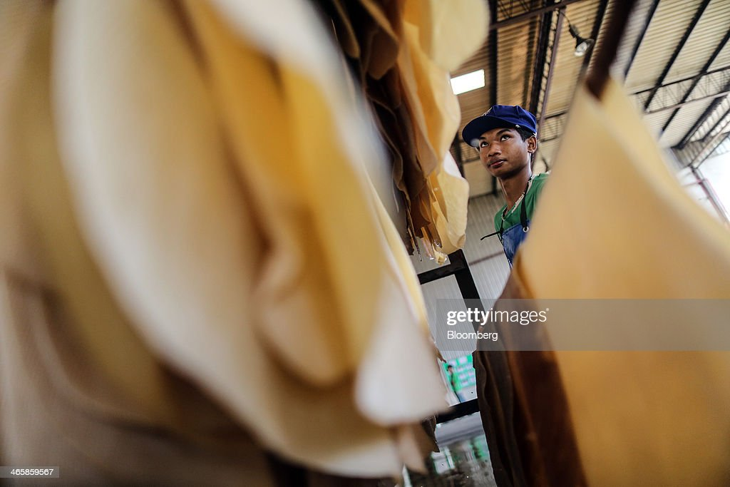 A worker hangs washed rubber sheets on racks for drying at the Thai Hua Rubber Pcl factory in Samnuktong, Rayong province, Thailand, on Wednesday, Jan. 29, 2014. Rubber production in Thailand, the world's largest exporter, may decline as growers from the main producing regions join protests seeking to overthrow the government, according to Von Bundit Co. Photographer: Dario Pignatelli/Bloomberg via Getty Images