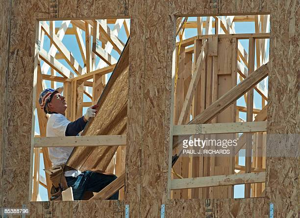 A worker hauls plywood to the roof during the construction of a new townhomecondominium in the Charleston Square complex built by Basheer Edgemoore...