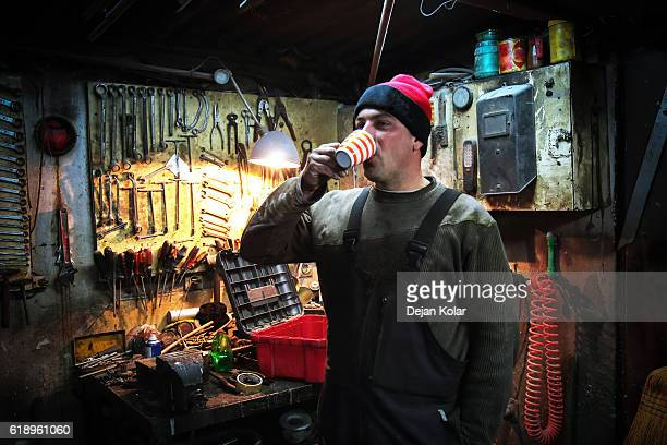 Worker having a coffee break at Vintage Auto Repair Shop.