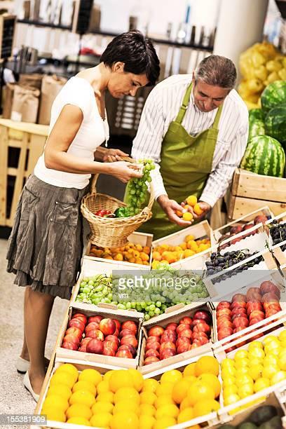 operaio aiuto choossing il diritto di produrre - bancarella di verdura foto e immagini stock
