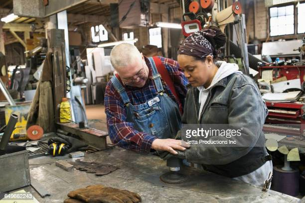 Worker helping colleague use sander in workshop