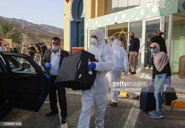 A worker helps a maskclad woman with her baggage as she prepares to leave a Dead Sea resort where she has been quarantined for 14 days approximately...
