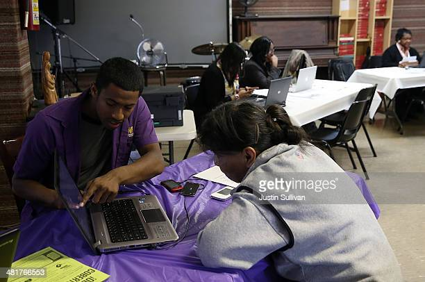 Worker helps an applicant register during a healthcare enrollment fair at the Bay Area Rescue Mission on March 31, 2014 in Richmond, California....